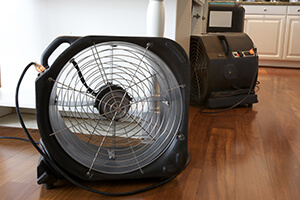 Home floors being aired out by commercial-sized fans due to flooding.