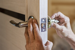 A handyman installing new door handles on a wooden door.