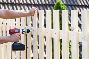 A handyman performing a home improvement project that entails building a wooden perimeter fence.