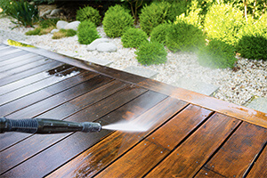 A professional power washing an outdoor wooden deck that needs to be refinished.
